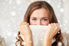 Young woman or teen girl pulling pullover collar. Winter, christmas and people concept - young woman or teen girl pulling up pullover collar over snow Stock Image