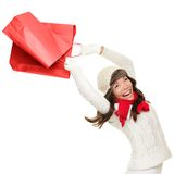 Winter and christmas shopping woman. Winter and christmas shopping. Woman holding red shopping bags happy, ecstatic and cheering with energy, Isolated on white Stock Photos