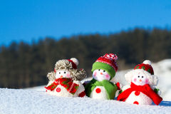 The winter, Christmas - three happy snowmen stand against the background of the blue sky. Royalty Free Stock Images