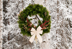 Winter Christmas Wreath. Christmas wreath hanging from snowy trees Stock Image