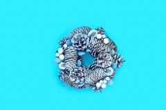 Winter and Christmas wreath with snow covered spruce pine fir, mistletoe, pine cones, cedar isolated on blue background royalty free stock images