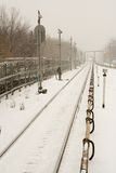 Winter at city. Snow falls. Railway tracks and vague silhouette of train Royalty Free Stock Image