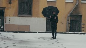 Winter in the city, bad weather. Young man standing under snowfall with umbrella. Young man standing under snowfall with umbrella holding plastic coffee cup stock footage