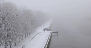 Winter in a city. Man is walking along the riverbank in snowy winter stock video footage