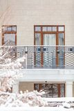 Winter city plot. Snow-covered house with balcony. Winter urban landscape. Modern house with a balcony and high windows on a quiet snowy day royalty free stock images