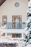 Winter city plot. Snow-covered house with balcony. Winter urban landscape. Modern house with a balcony and high windows on a quiet snowy day royalty free stock image