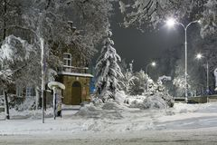 Winter in the city, snow-covered trees and signs, white streets and sidewalks. Winter season Royalty Free Stock Photo