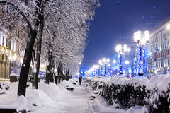 Winter city street with trees and benches covered in snow and la stock photo