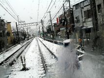 Winter in the City (Tokyo, Japan). A perspective of a local railroad from a fogged glass in a snowy winter day (Tokyo, Japan stock photo