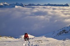 Winter climbing in the mountains. Breathtaking panorama of mountains that seems to be floating above the clouds. Example of winter hiking royalty free stock photos