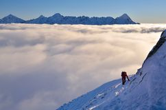 Winter climbing in Tatra mountains. Hiking and climbing on snow in high mountains with summits over clouds in the background royalty free stock images