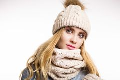 Winter close-up portrait of attractive young blonde woman wearing beige warm knitted hat with fur pompom and scarf. Snood. Girl looking at camera on white royalty free stock photo