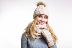 Winter close-up portrait of attractive young blonde woman wearing beige warm knitted hat with fur pompom and scarf snood. Girl stock photos