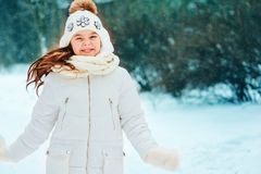 Winter close up portrait of cute dreamy child girl in white coat, hat and mittens stock photos