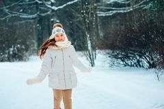 Winter close up portrait of cute dreamy child girl in white coat, hat and mittens royalty free stock images