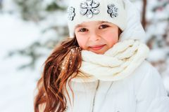 Winter close up portrait of cute dreamy child girl in white coat, hat and mittens playing outdoor in snowy winter forest stock photos