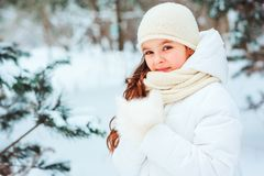 Winter close up portrait of cute dreamy child girl in white coat, hat and mittens royalty free stock image