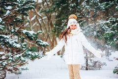 Winter close up portrait of cute dreamy child girl in white coat, hat and mittens stock images