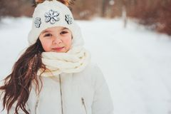 Winter close up portrait of cute dreamy child girl in white coat, hat and mittens royalty free stock photo