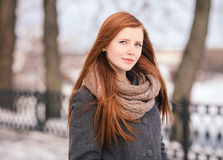 Winter closeup portrait of a cute redhead lady in grey coat and scarf posing in the park. Winter closeup portrait of a cute redhead lady in grey coat and scarf royalty free stock photography