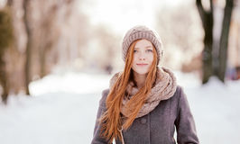 Winter closeup portrait of a cute redhead lady in grey coat and scarf posing in the park Royalty Free Stock Photography