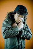 Winter clothes. Portrait of a 21 year old man with a winter coat and hat on, holding the coat closer together at the neck to keep warm.  Distant expression Royalty Free Stock Image