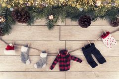 Winter clothes hanging up. A tree branches and a wooden table in background. royalty free stock photography