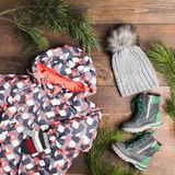 Winter clothes with jumpers, knitted hat and gloves and boots ov. Er wooden background with fir tree decoration, flat lay Royalty Free Stock Photos