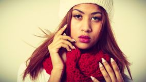 Mulatto woman wearing warm winter clothing. Winter clothing, fashion concept. Beautiful young mulatto woman wearing red woolen scarf white cap. Mixed race girl Royalty Free Stock Photography