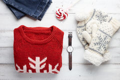 Winter clothing style. Christmas clothing style set with winter knitted sweater, jeans, cap, mittens, watches and lollipop Stock Image