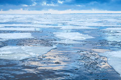 Winter coastal landscape with floating ice fragments Stock Photos