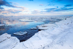 Winter coastal landscape with floating ice fragments Stock Photography