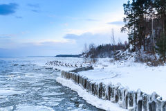 Winter coastal landscape with floating ice and frozen pier Stock Photos