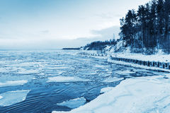 Winter coastal landscape with floating ice and frozen pier Stock Photography