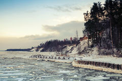 Winter coastal landscape with floating ice and frozen pier Royalty Free Stock Images