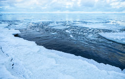 Winter coastal landscape with floating ice on still sea water Stock Photo