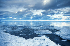 Winter coastal landscape with floating melting ice fragments. Winter coastal landscape with floating ice fragments on still cold blue water. Gulf of Finland royalty free stock images