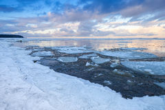 Winter coastal landscape with ice fragments on still water Stock Photo
