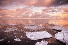 Winter coastal landscape with melting ice fragments Stock Images