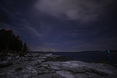 Winter coastline landscape at night from Tobermory. Limestone rocks, with ice and snow, cedar tree silhouettes, the green harbor light and stars , constellations Royalty Free Stock Photography