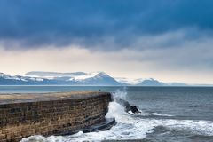 Winter at the Cobb. A closer shot along the upper wall looking east from the Cobb at Lyme Regis towards the snow-dusted Jurassic coastline with heavy clouds royalty free stock images