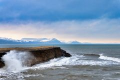 Winter at the Cobb. Looking east from the Cobb at Lyme Regis along the upper wall towards the snow-dusted Jurassic coastline stock photography