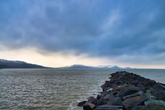 Winter at the Cobb. Looking east from the Cobb at Lyme Regis over the breakwater rocks towards the Jurassic coastline stock photography