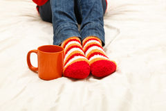 Winter coffee home. Feet in colorful socks and coffee cup, concept of home warmth, comfort and laziness Royalty Free Stock Photos