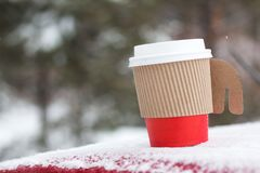 Winter coffee in paper cup. Winter coffee in red paper cup in outdoors with snow Royalty Free Stock Image