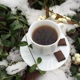 Winter coffee: white cup with black coffee and a saucer with chunks of chocolate. On a  snow background Royalty Free Stock Photo