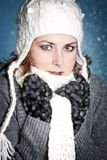 Winter cold. Beautiful girl with warm winterclothes in the snow Stock Image