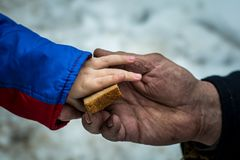 The child gives the man a piece of rye bread. royalty free stock photography
