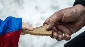 The child gives the man a piece of rye bread. royalty free stock images