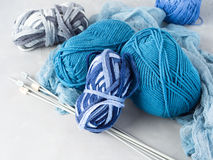 Winter cold color woolen yarn with knitting needles. Winter color wool yarn with knitting needles. Blue palette and gray clews Royalty Free Stock Photos